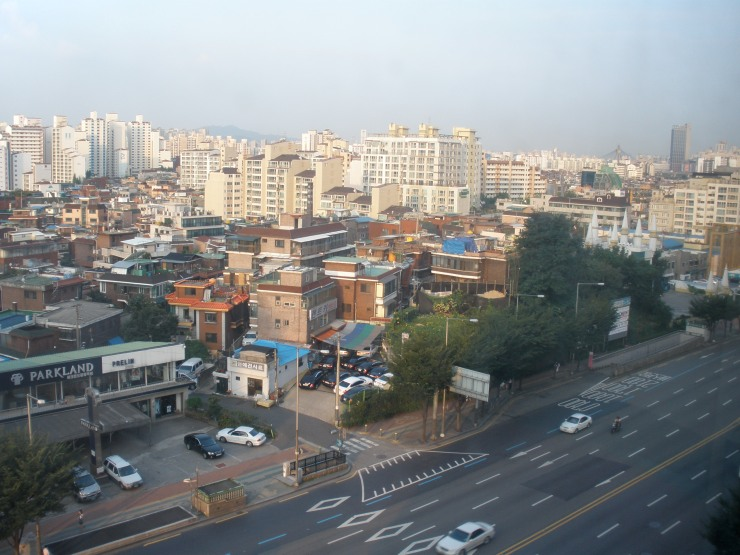 A view from my apartment window shows the stark contrast between older Korean buildings and the modern apartment complexes and high-rise office buildings adjacent to them.