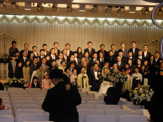Modern wedding: An example of how much Korean culture embraces the family unit: instead of having a small wedding party and taking photos with immediate family members only, Koreans have their photographer gather every friend and family member together for one big picture after the wedding.