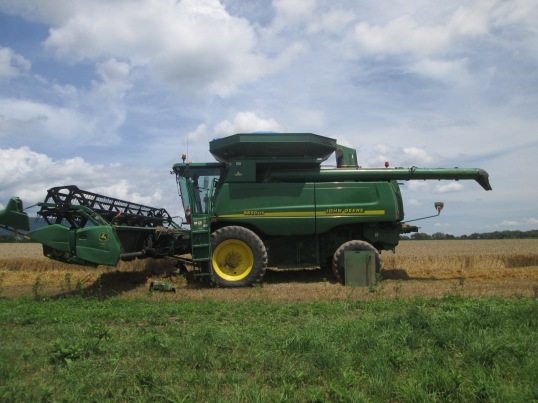The large combine prepared to harvest a field of wheat